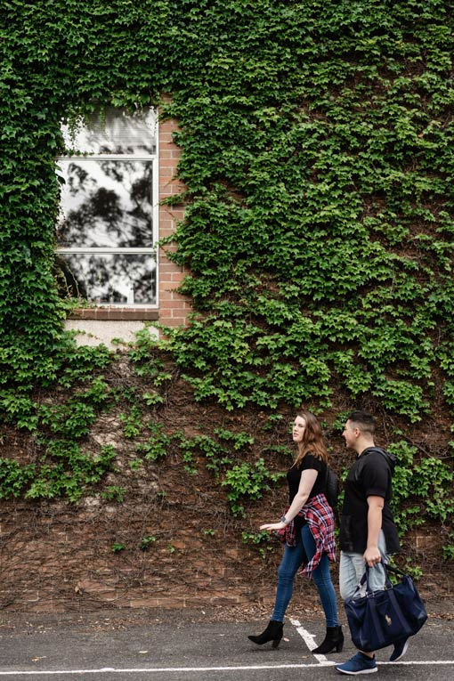 Students walking past a building covered with dense green plants.